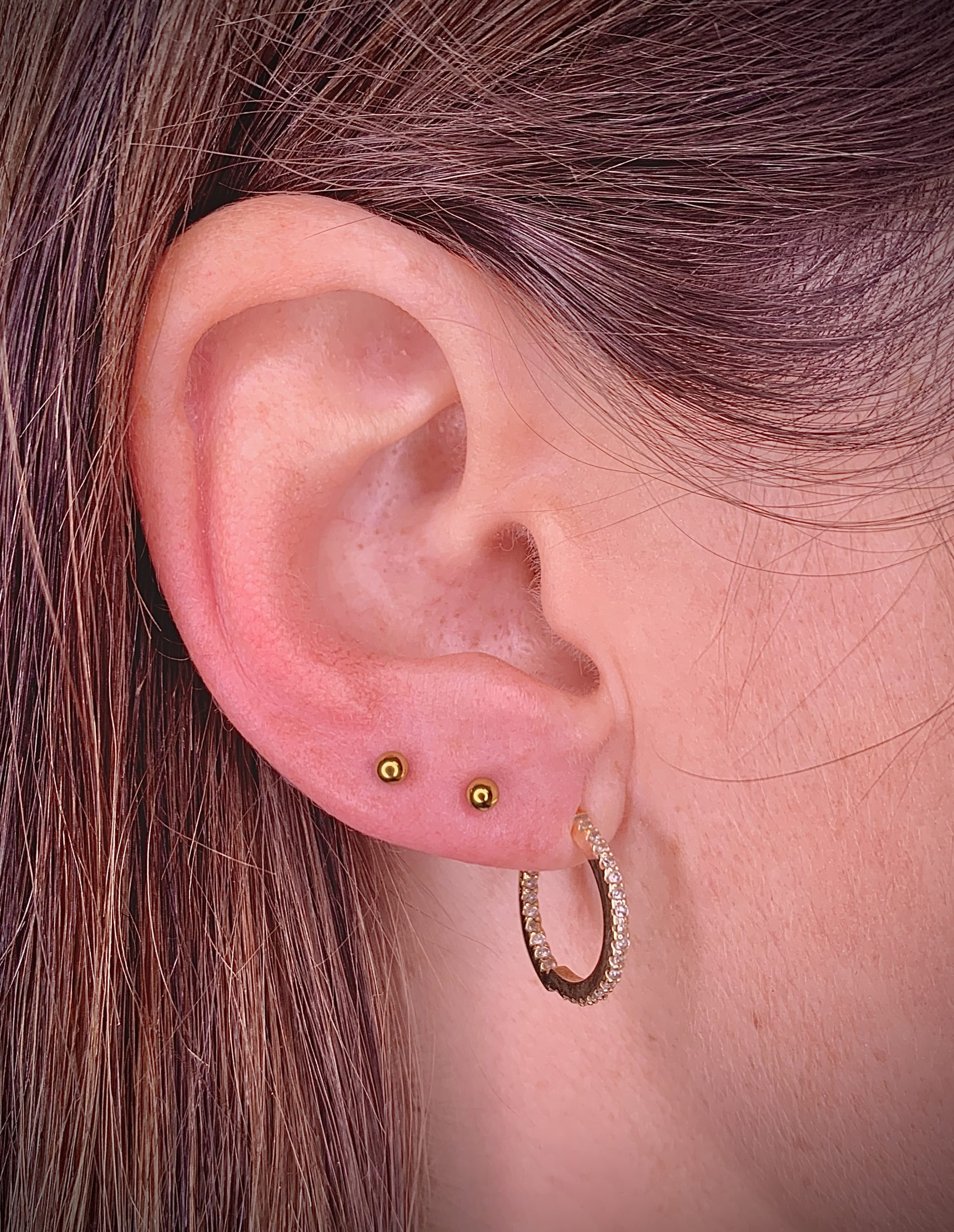 Ear Piercing two upper lobes with a titanium jewelry anodized in gold color. Piercing Barcelona